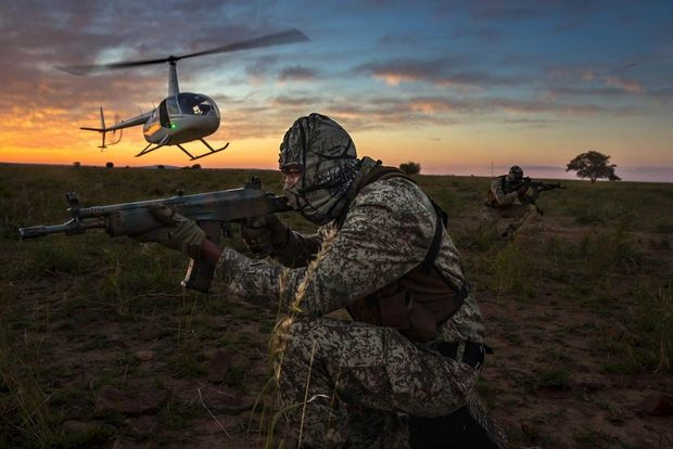 A two-man security team deploys by helicopter at sunset for anti-poaching duties on the world's largest rhino breeding ranch at Buffalo Dream Ranch, Klerksdorp, South Africa.