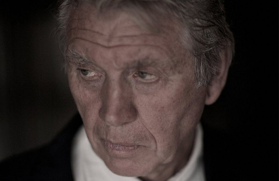 Sir Don McCullin, dressed in a white shirt and black jacket, poses for a portrait shot.