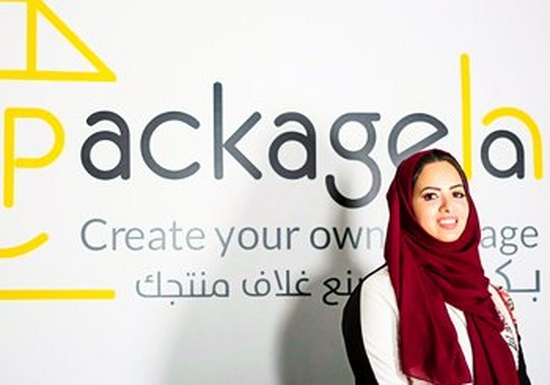 A smiling Doaa bin Thabit stands in front of the logo for Packageha.