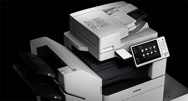 Canon office multi-function printer with touchscreen and a black background.