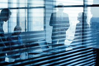 A blue-tinged view through a window with slatted blinds into a meeting room with the shadow/outlines of four people standing and sitting around a table with a laptop.