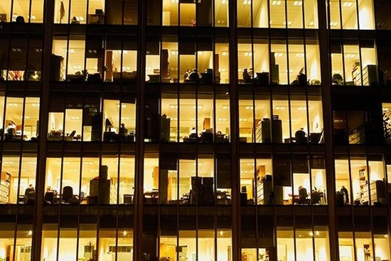 A view into an office building at night, with the windows lit up in yellow and office equipment in silhouette.