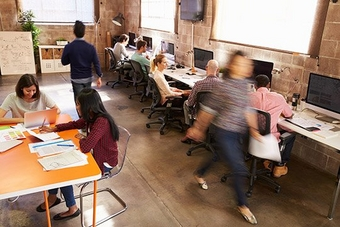 A casual office environment with people working at their computer desks or a communal table, and a blurry woman rushing past.