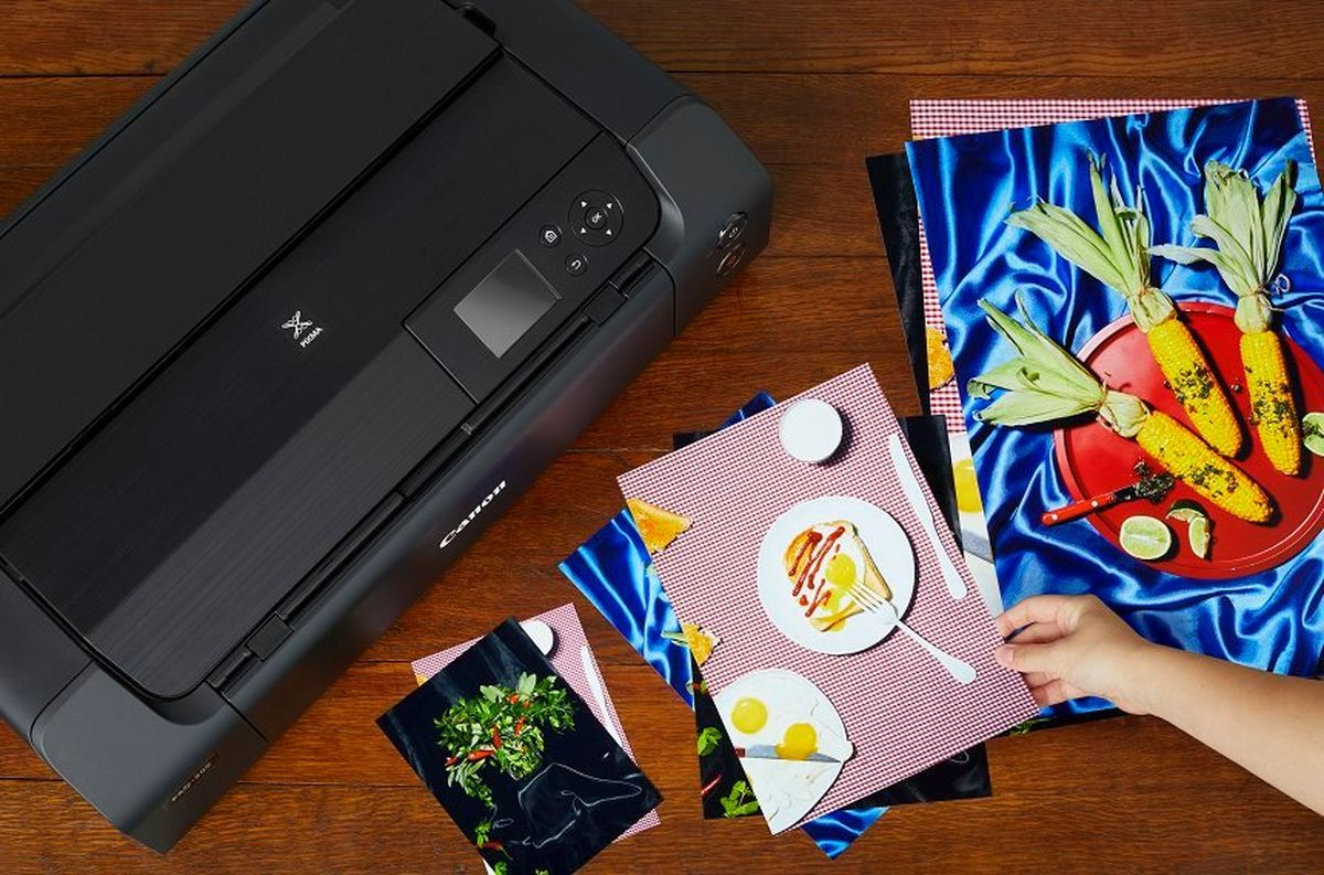A woman's hand holds one of a number of borderless prints of different sizes, on a tabletop next to a Canon Pixma-pro-200 printer.