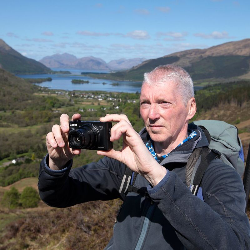 Alan Rowan stands on the side of a hill, with yellow gorse bushes, grassy fields and a river in the valley behind him. He holds a compact camera to take a photo of the natural view.