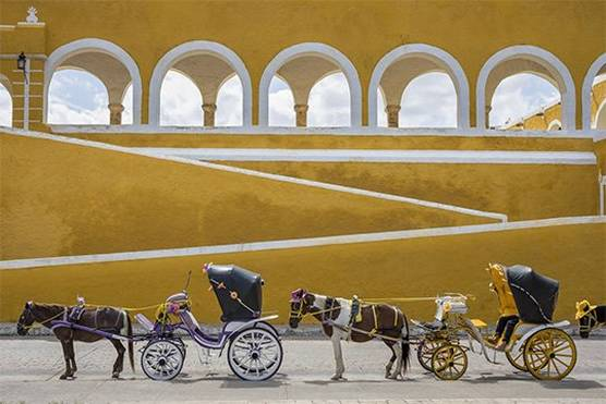 Horses and carriages awaiting passengers by the Convent in Izamal, Mexico.