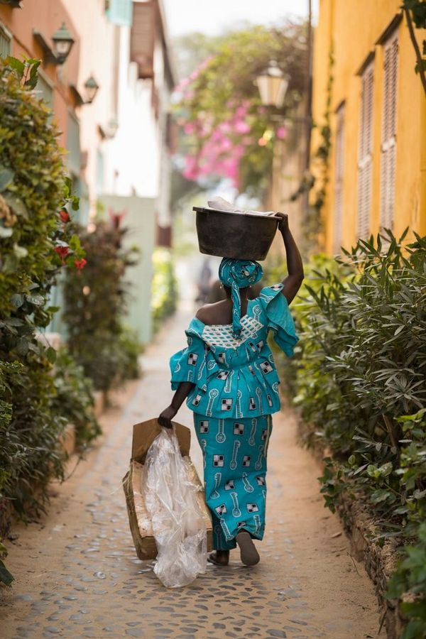 A woman wearing a patterned turquoise outfit, walking down an alley on Gorée Island, Senegal.