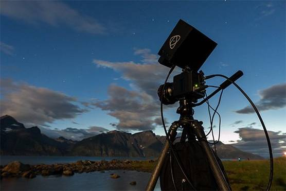 A Canon ME20F-SH cinema camera attached to a tripod beside a mountain lake.