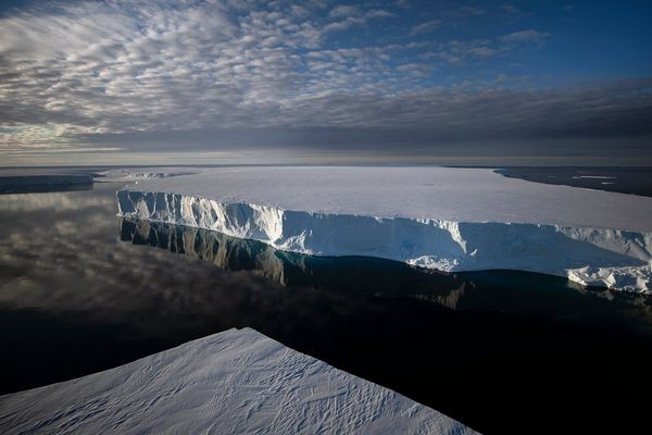 A vast ice shelf casts a reflection onto the waters of Antarctica. Taken by Lucia Griggi.
