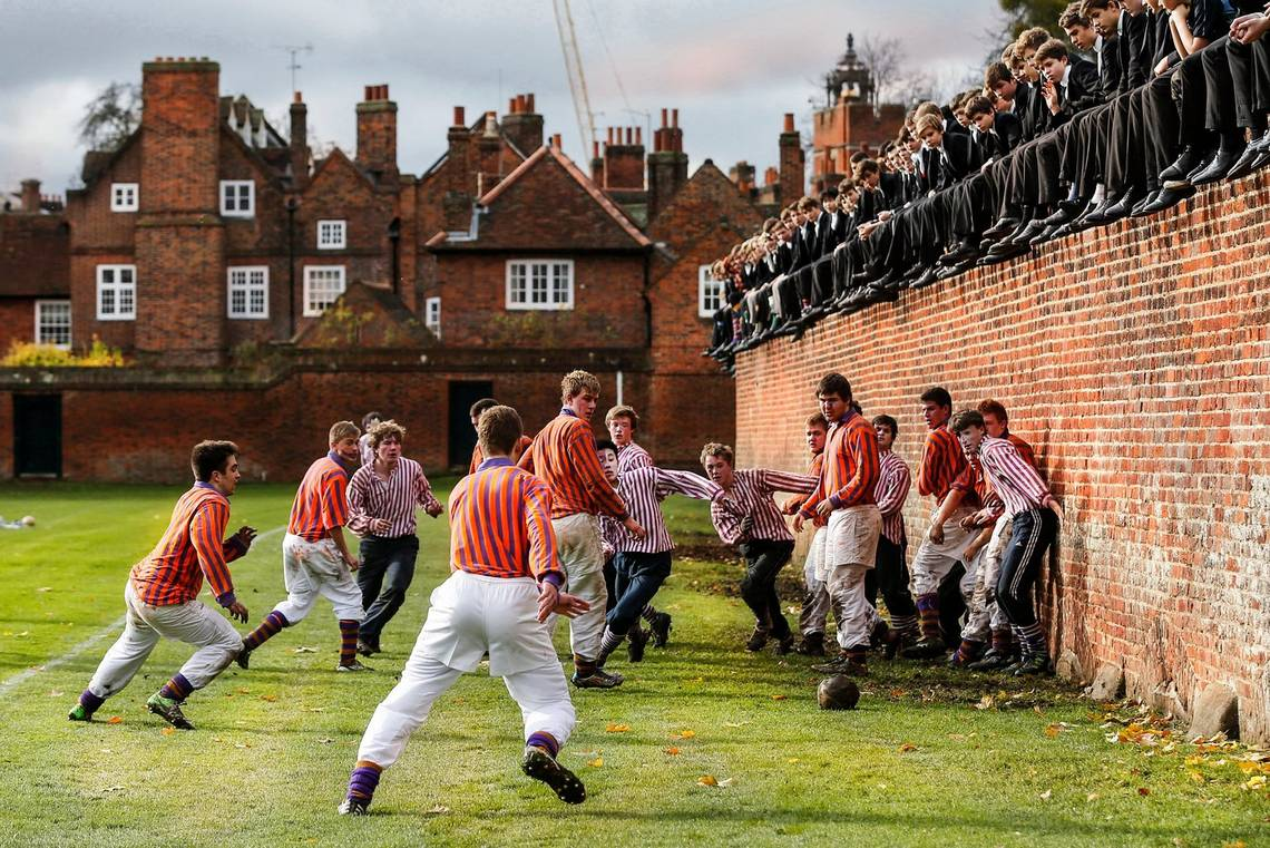 Pupils at Eton College play football dressed in traditional attire and watched by other pupils from a wall above. Photo by Canon Ambassador Eddie Keogh.