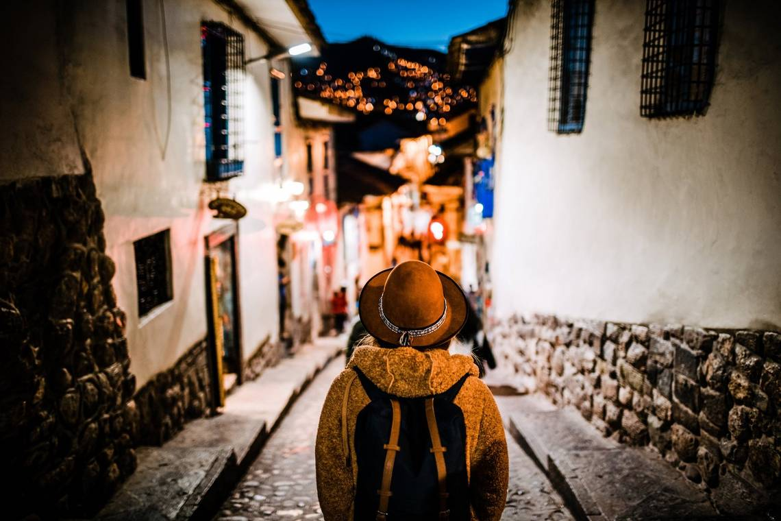 A tourist, wearing an overcoat, backpack and a hat, pictured from behind facing an old cobbled street at evening with lights twinkling on a dark hill in the background.