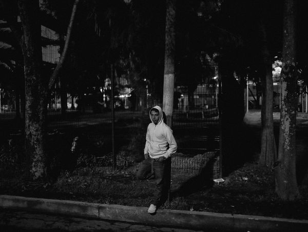 A youth wearing a hoodie leans against a lamppost in front of a tree-filled urban park in the evening.