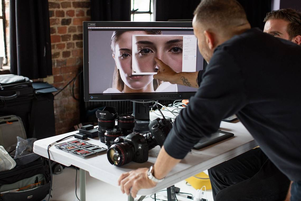 A man leans over a desk and points at an image of a woman's face on a monitor. A Canon camera and lenses are also on the desk.