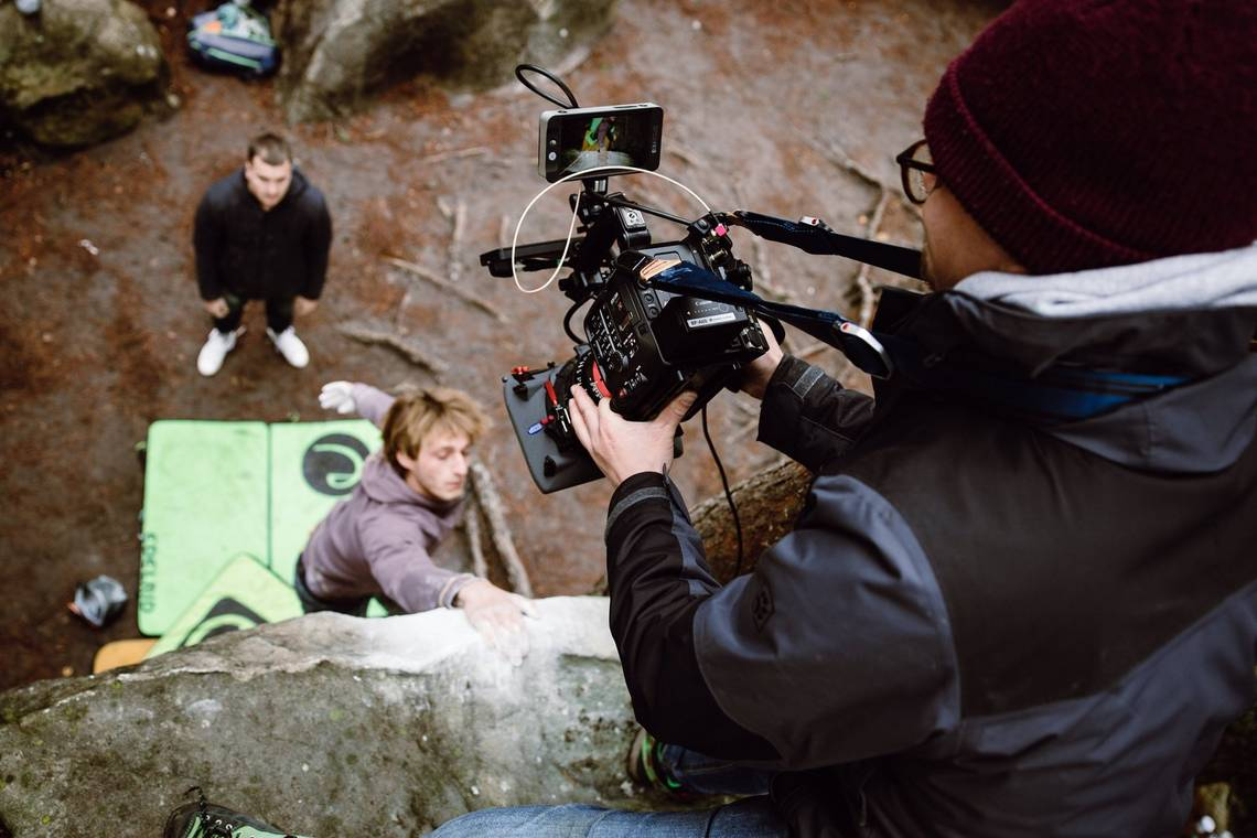 Filmmaker Nicolai Deutsch kneels on the edge of a ledge filming two rock climbers with a Canon EOS C500 Mark II.