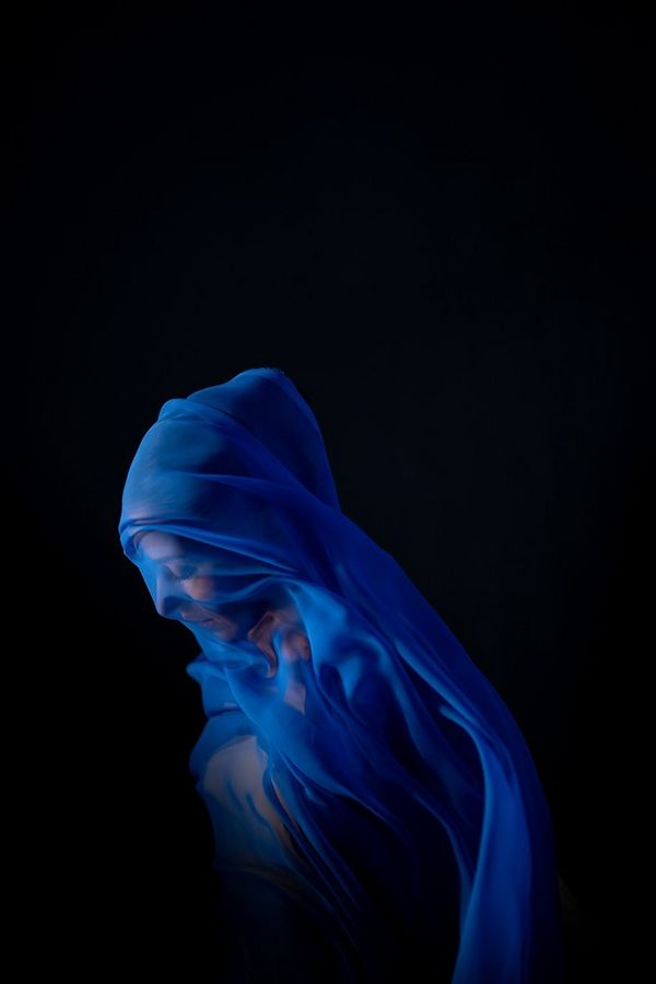 A side profile of a woman draped in sheer blue fabric by Canon Ambassador Clive Booth.