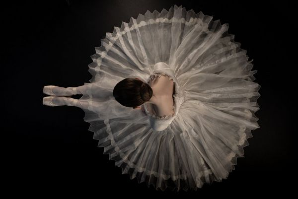 An overhead shot of a seated ballerina in a white tutu by Canon Ambassador Clive Booth.