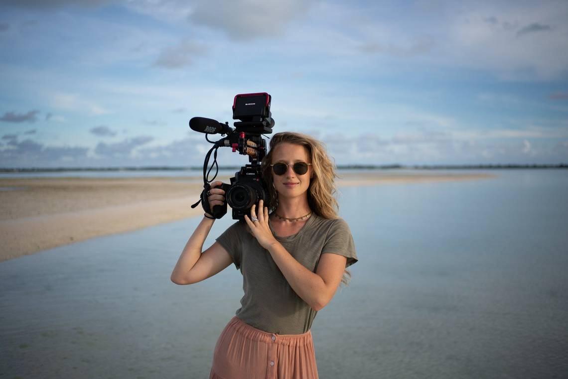 Filmmaker Alice Aedy on the coast of Kiribati holding a Canon EOS C300 Mark II.