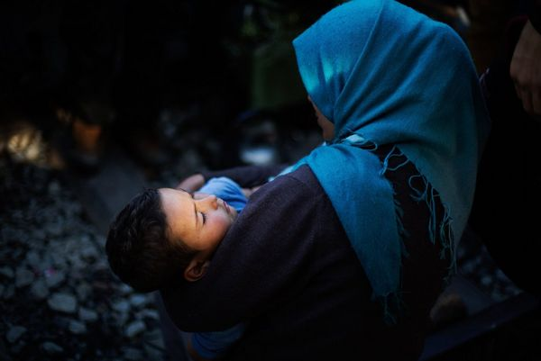 A Syrian woman in a blue headscarf cradles a child at the Idomeni refugee camp in Greece.