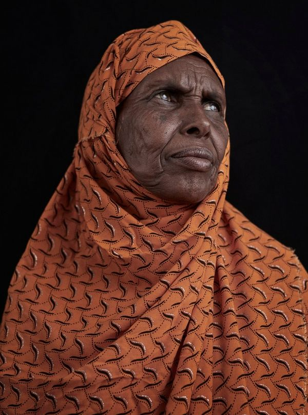 A portrait taken in rural Somaliland of a village elder in an orange patterned headscarf.