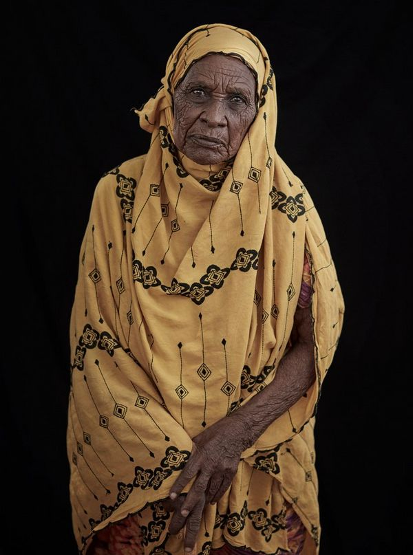 A portrait taken in rural Somaliland of an elderly woman in a yellow patterned dress.