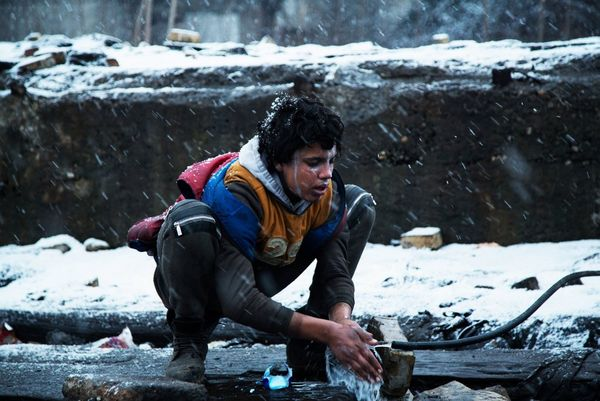 A young Afghan boy washes himself in the only running water available outside an illegal squat in Serbia.