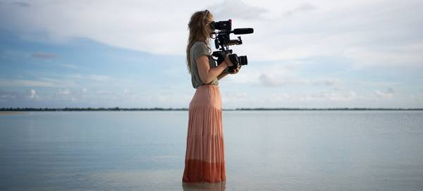 Filmmaker Alice Aedy standing in the sea holding a Canon EOS C300 Mark II.