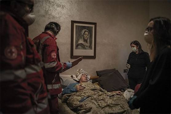 A man lies in bed surrounded by Italian Red Cross volunteers. A painting of the Virgin Mary hangs on the wall. Photo by Fabio Bucciarelli.