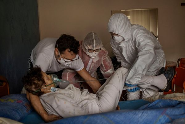 Three people in protective gear help lift a woman with Covid-19 onto her bed. Photo by Fabio Bucciarelli.