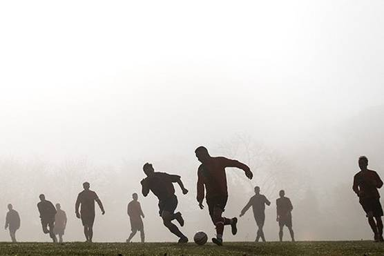Footballers silhouetted against the early morning fog.