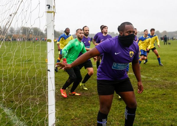 Players prepare to defend an incoming shot during a game at Hackney Marshes, East London, England.