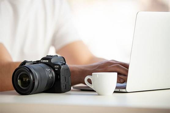 A Canon EOS R6 camera on a desk next to a man typing on a laptop.