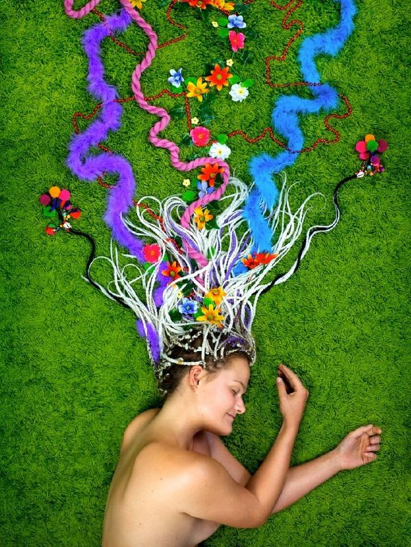 A still from a video self-portrait of Neoza Goffin. She is lying on grass with colourful ribbons in her hair.