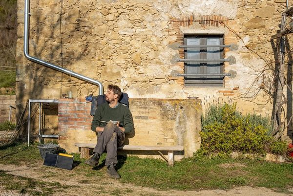 Daniel Etter sitting in the sun outside his farmhouse.
