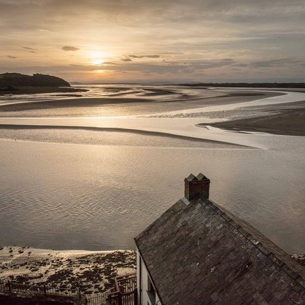 The sun sets in front of Dylan Thomas Boathouse in Laugharne, Dyfed, Wales.