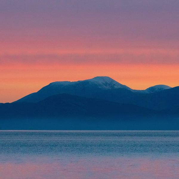 The sky is streaked orange and pink behind the outline of Ben Nevis in the Highlands, Scotland.