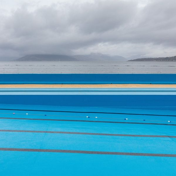 The bright blue waters of Gourock Outdoor Pool in Inverclyde, Scotland, under grey storm clouds.
