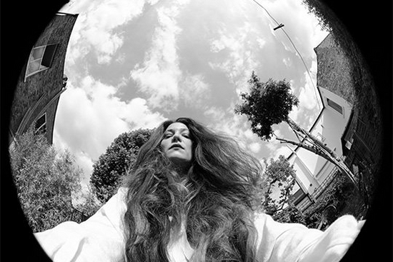 A black-and-white image shot with a fisheye lens of Canon Ambassador Wanda Martin looking down at the camera, her long hair falling around her shoulders.