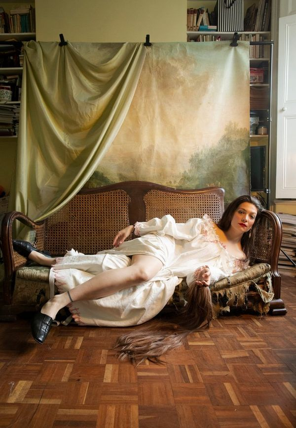 Wanda Martin reclines on a low sofa, a sheet of material clipped to a rail behind her.