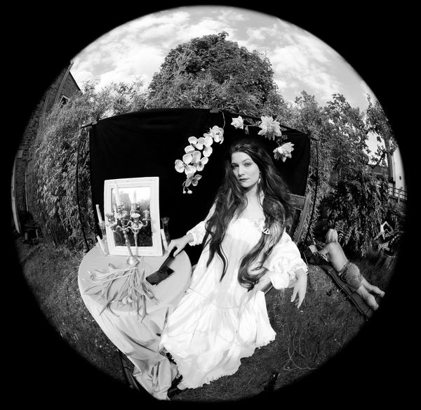 A black-and-white image shot with a fisheye lens of Wanda Martin recreating Dante Gabriel Rossetti's Lady Lilith in her garden.