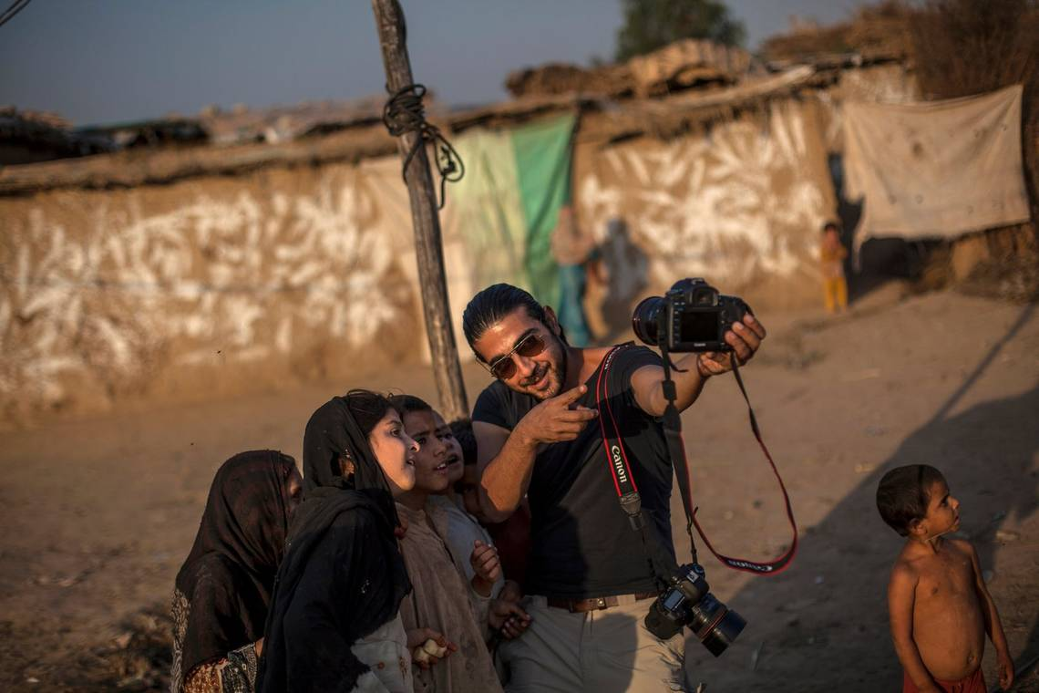 Canon Ambassador Muhammed Muheisen explaining how his camera works to a group of Afghan children.