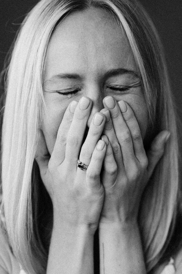 A black-and-white portrait of a woman crying, her face in her hands.
