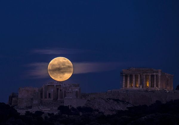 A full moon rising above the Acropolis of Athens, Greece.