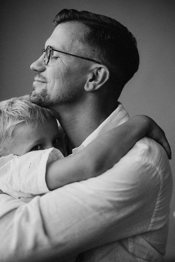 A black-and-white portrait shot of a father and son embracing.