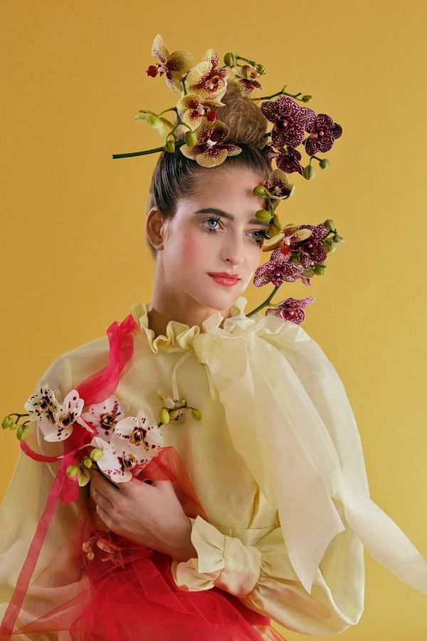 A model wearing pastel yellow and pink lace holding flowers.