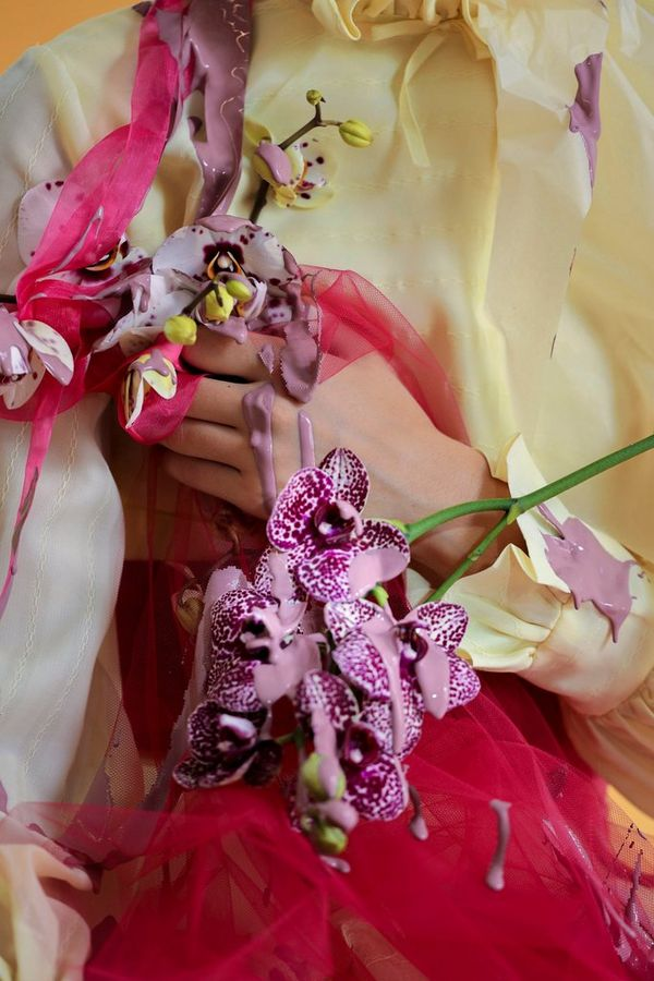 A close-up of a model wearing an abstract outfit, adorned by flowers with purple paint poured on her.