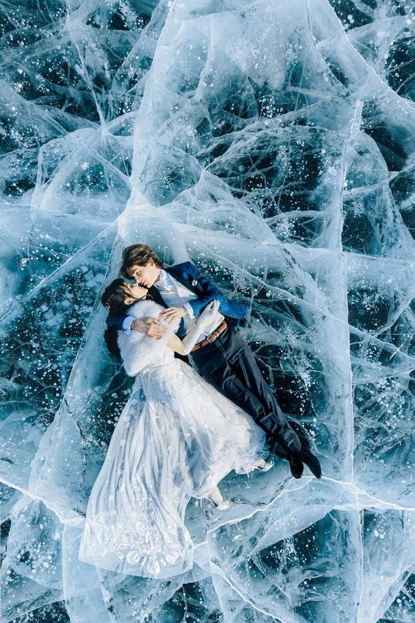 A married couple lie in their finery on a frozen, cracked lake in Russia.