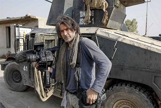 Filmmaker Olivier Sabril standing in front of a tank in Mosul, Iraq, with a Canon EOS C300 Mark II video camera.