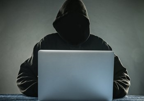A hooded figure sits behind a laptop.