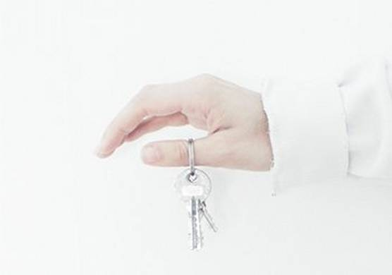 An outstretched arm and hand, dangling a set of keys from the thumb.