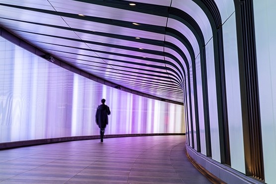 Person walks through pink lit corridor